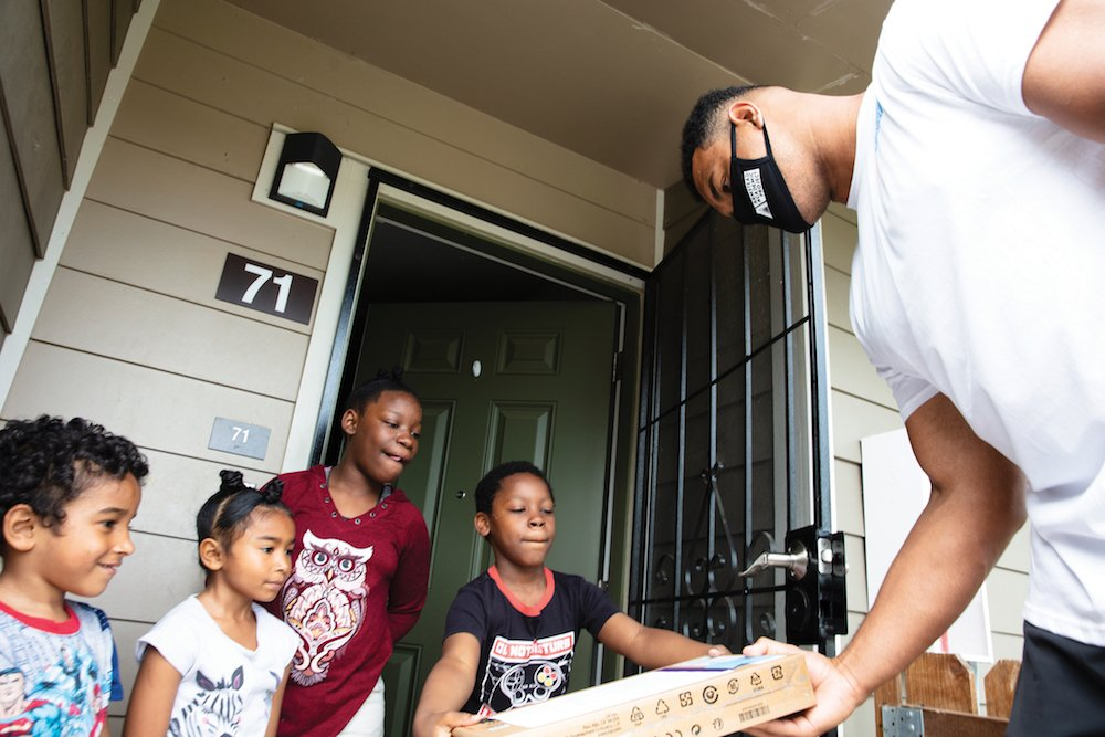 Armstead distributes Chromebooks to kids at a Mercy Housing community on June 15. (Photo by Smeeta Mahanti)