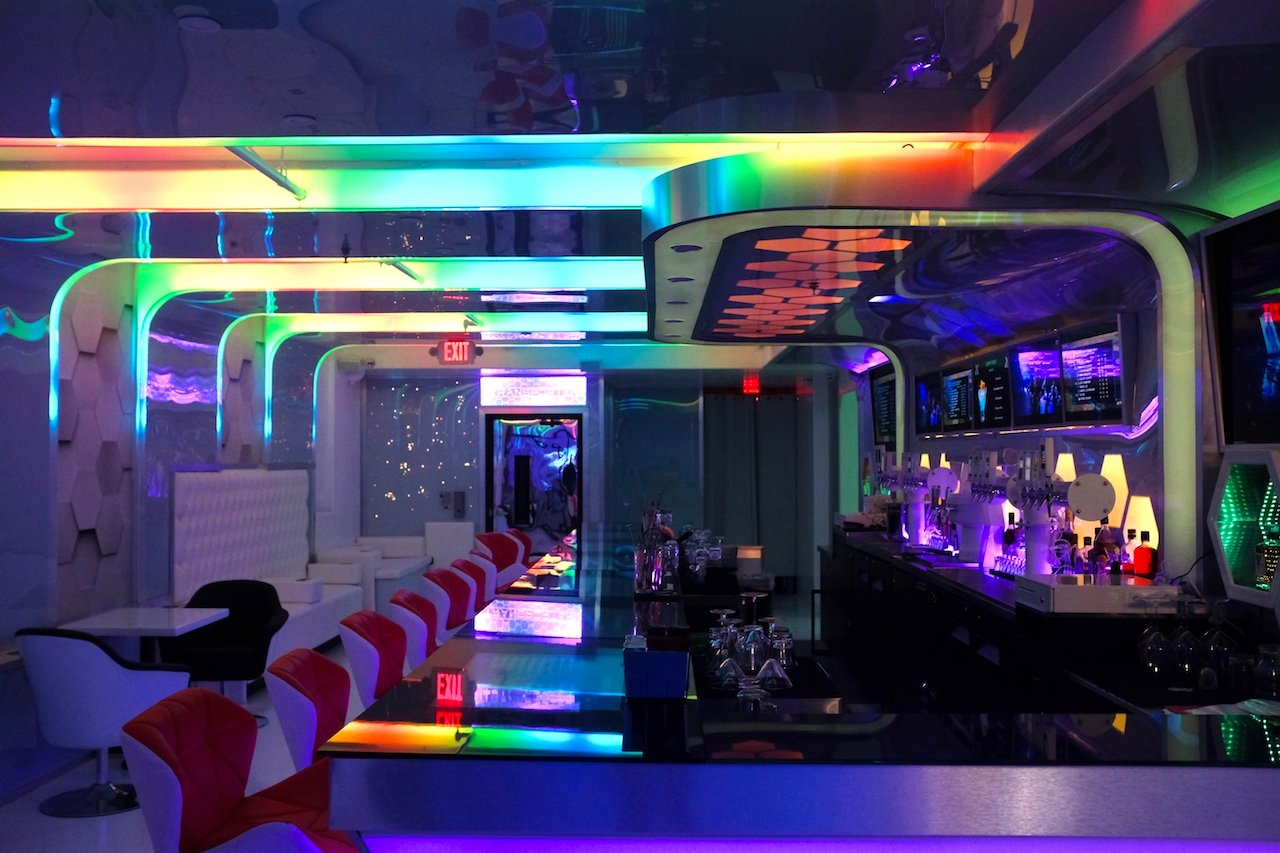 The downstairs bar at KoJa Kitchen features white tufted booths and multicolored LED lights.