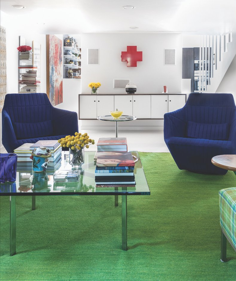 The Popp family room includes royal blue Ligne Roset armchairs, a red Cappellini cross medicine cabinet and a Ptolomeo bookstand by Bruno Rainaldi. (Photo by Kat Alves)