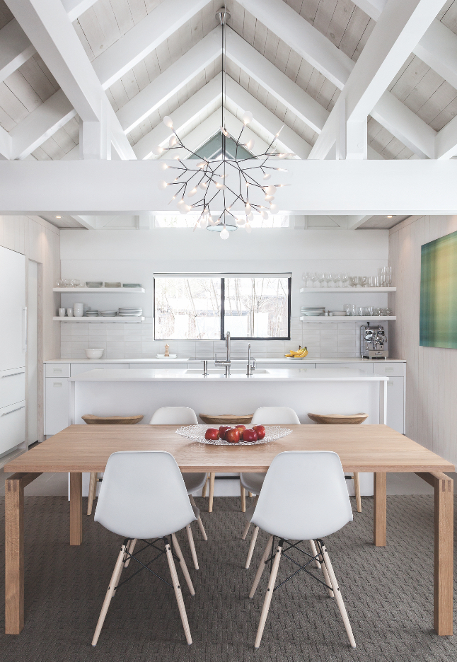 To create a Scandinavian beach house vibe requested by the residents, Popp used light materials like whitewashed pine and placed pieces like white Eames side chairs in the kitchen-dining area of a Tahoe City home. (Photo by Kat Alves)