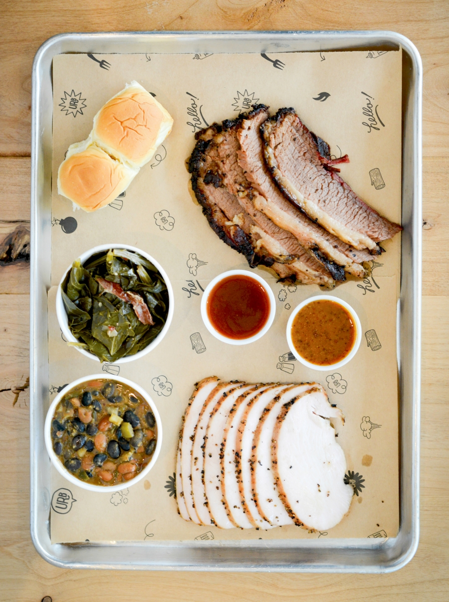 Collard greens, barbecue beans, Hawaiian rolls, and slices of brisket and turkey fill a tray at Urban Roots.