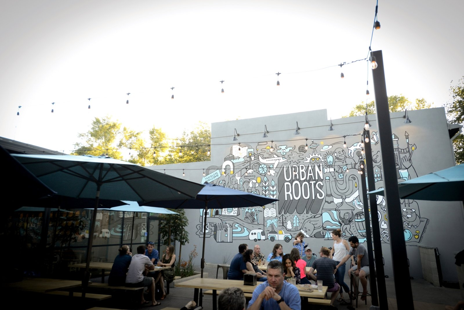A large mural with illustrations of objects like a passport and airplane to represent travel and sprouting hops that pay tribute to Sacramento's agricultural roots decorates the expansive outdoor patio.