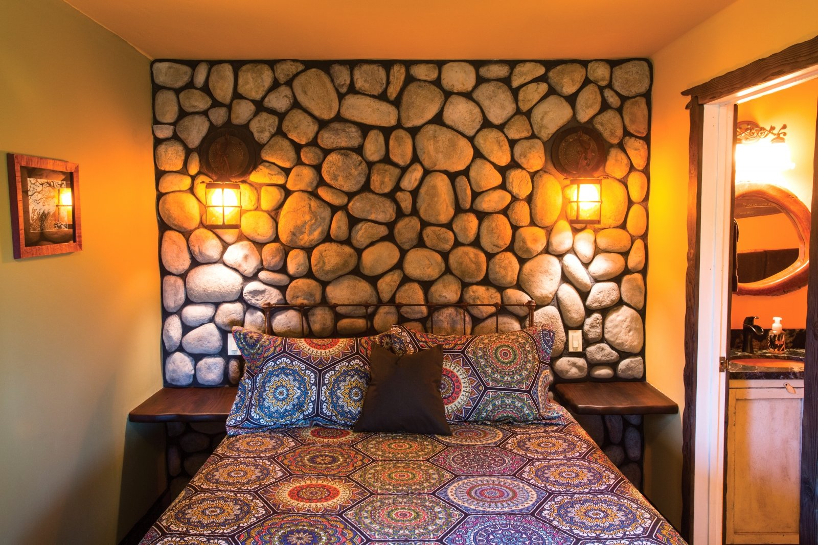 The Little Hobbit House's cozy bedroom with a dramatic stone wall (Photos by Jeremy Sykes)