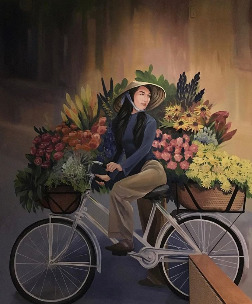 A Vietnamese woman sells blossoms by bike, including lotus flowers, crystal gems and lilies, in this mural on the restaurant's ground floor. (Photo by Madelyne Joan Templeton)