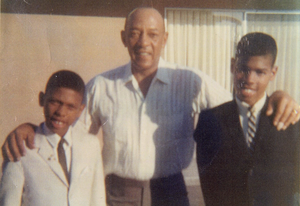 Olympic champion Jesse Owens is flanked by Cornel (left) and his older brother Cliff in the West family's backyard in 1967. (Photo courtesy of the West family).