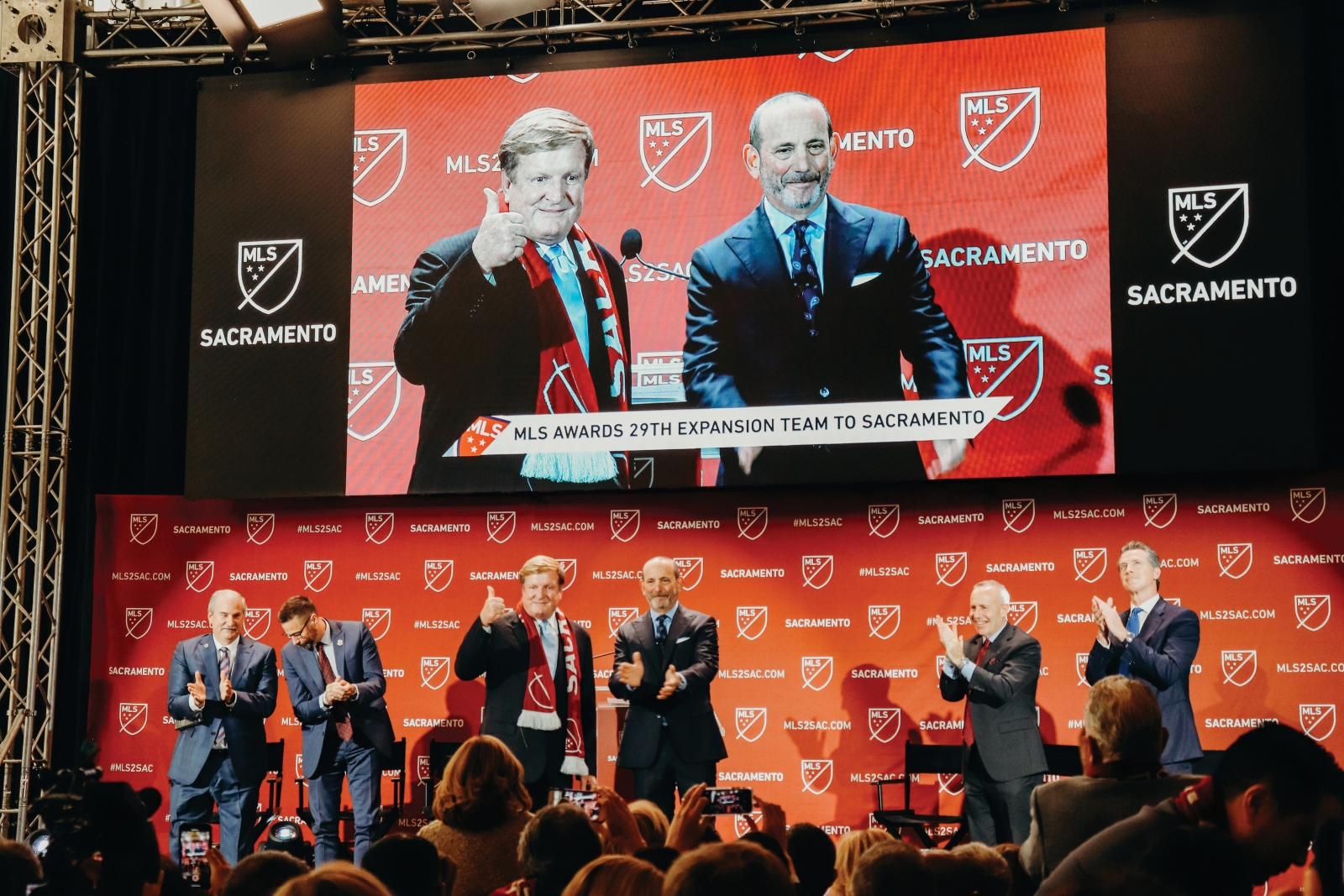 From left, Republic FC lead investor Ron Burkle, Major League Soccer commissioner Don Garber and Sacramento Mayor Darrell Steinberg celebrate as the Republic is announced as MLS's newest team on Oct. 21. (Photo courtesy of Downtown Sacramento Partnership)