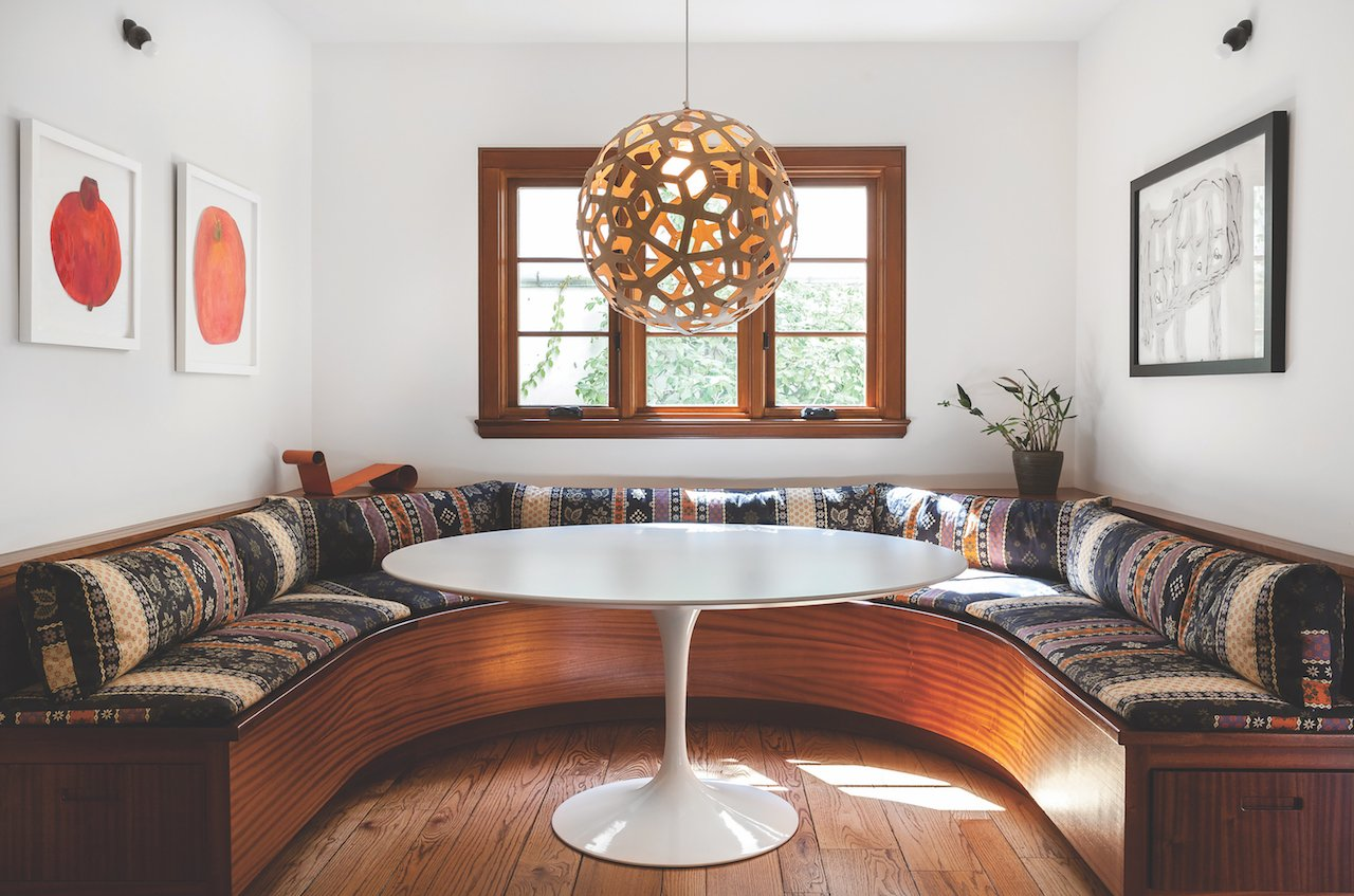 """The family wanted a rustic-modern look,"" says Popp of this Land Park home remodel. To achieve that feel, he blended warm wood pieces (like the curved mahogany banquette he designed for the dining nook) with cool contemporary lighting (like the Roll & Hill chandelier in the living room, below). (Photos by Kat Alves)"