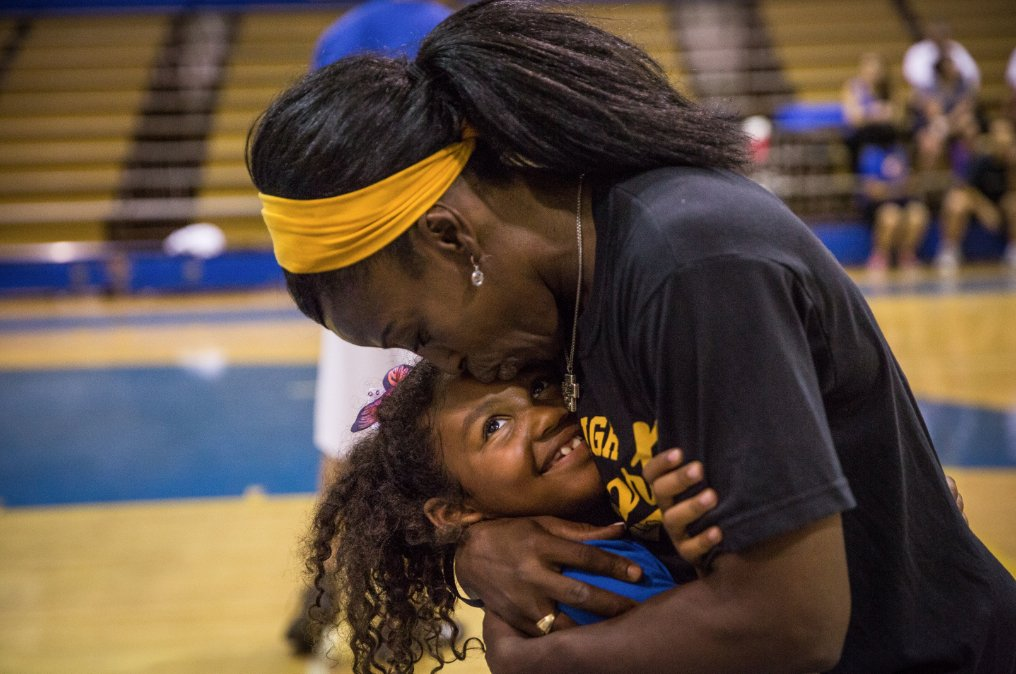 Bolton embraces her daughter, Hope, during a basketball camp session at Grant High. The 7-year-old is her mom's frequent sidekick and travel companion. (Photo by Max Whittaker)