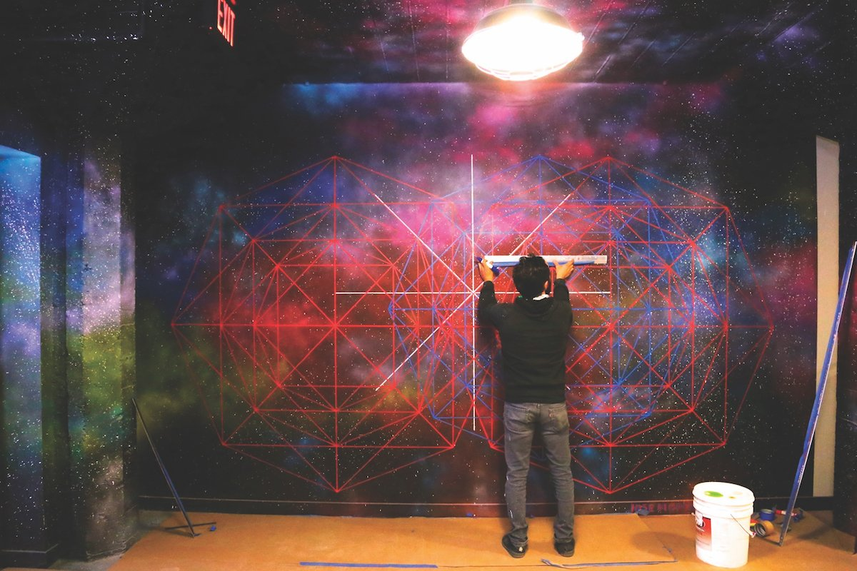 WAL artist Jose Di Gregorio works on a mural that spans the second-floor elevator lobby. (Photo courtesy of CFY Development)