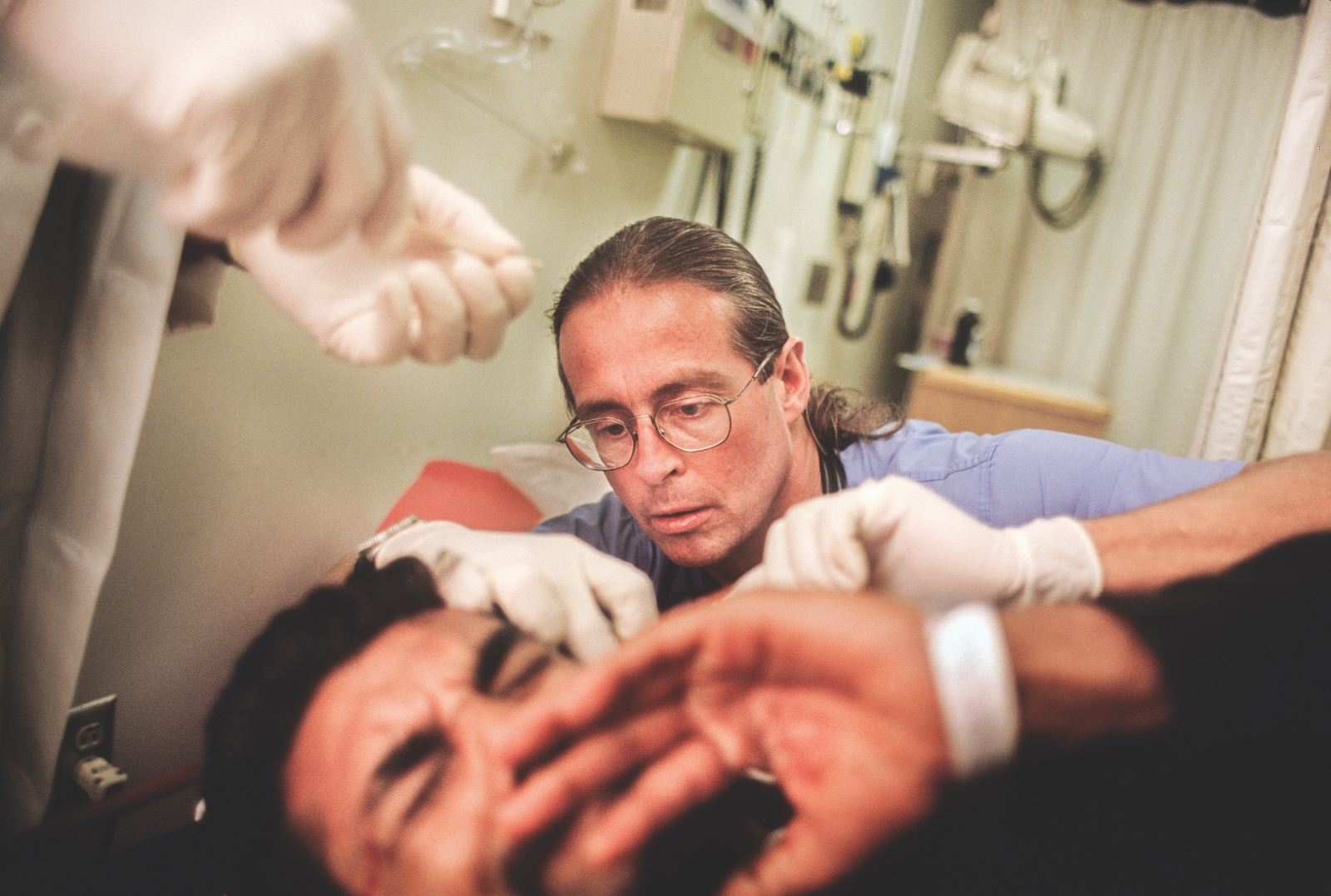 Wintemute performs a surgical procedure on a patient at the UC Davis Medical Center in 1997. (Photo by Mark Richards)