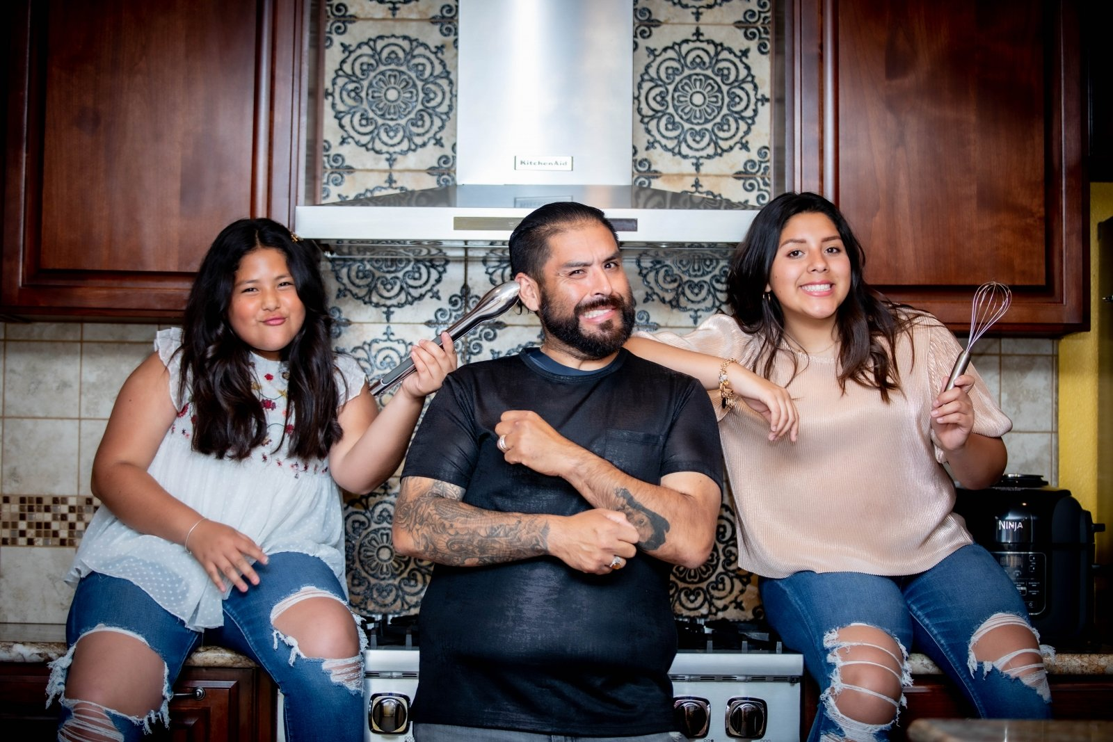 "Lisandro ""Chando"" Madrigal and his two daughters share homestyle how-tos for Mexican meals on their weekly Facebook Live show. (Photo by Fotografia de Walden)"