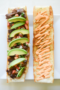 The pepito sandwich with flank steak, salsa,  avocado slices, refried beans and crushed  chipotle peppers on a baguette.