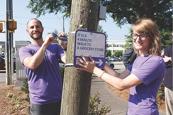 In Raleigh, North Carolina, Matt Tomasulo, left, launched a guerrilla wayfinding movement in an effort to encourage more people to walk. (Photo courtesy of Walk [Your City])