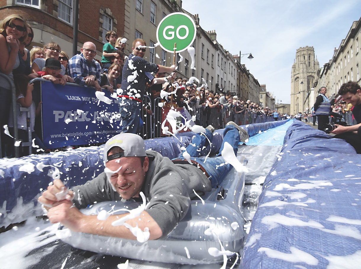 An artist in Bristol, England, used crowdfunding to raise enough money to place a massive, block-long waterslide on a city street. 96,000 people signed up to ride it. (Photo by Luke Jerram)