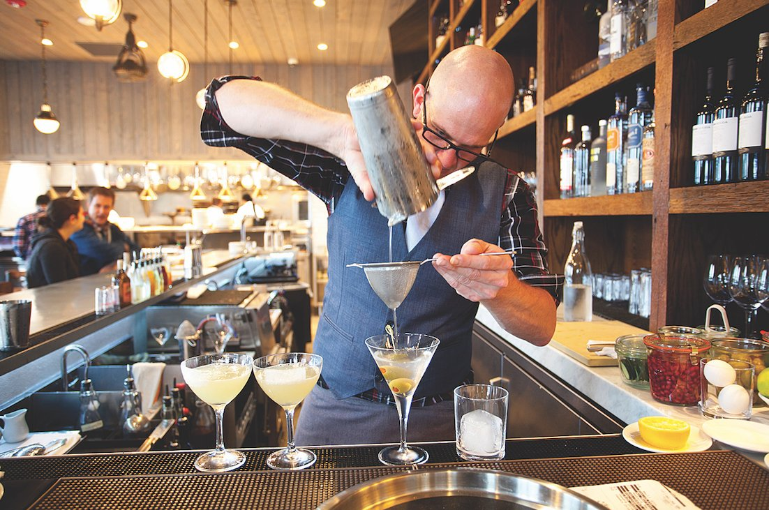 Bartender Stephen Dopkins crafts a Hawks Martini, which is made with Tito's Handmade Vodka and blue-cheese-stuffed olives.