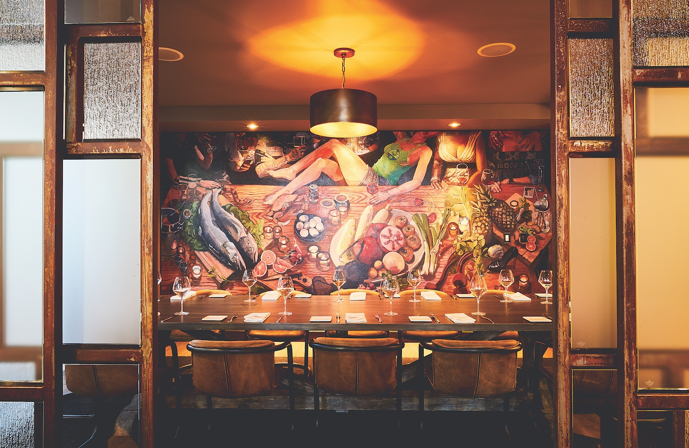 A canvas mural by Sacramento artist Ryan Seng depicting a meal sourced from local purveyors like Passmore Ranch and Del Rio Botanical fills the back wall of the private chef's table room at Grange to express the restaurant's farm-to-fork focus. (Photo by Aubrie Pick)