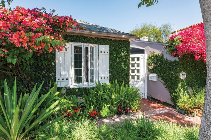 Mature coral and red bougainvillea frame the creeping fig-covered house. Society garlic, red begonias and ferns fill beds in front of the house.