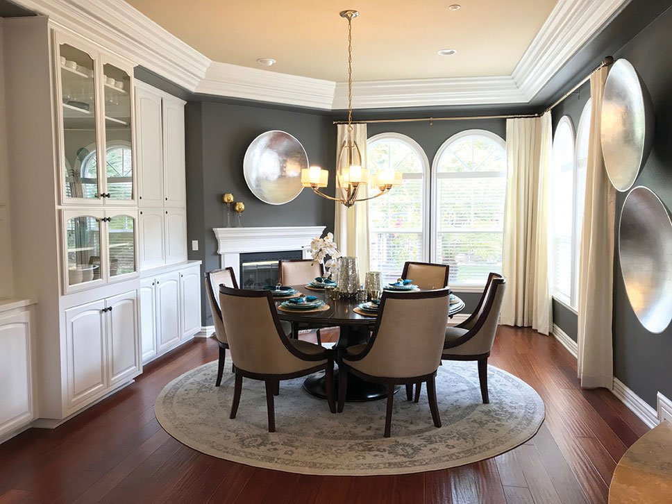 silver leaf wall art in a gray wall dining room with white trim designed by Nikki Klugh
