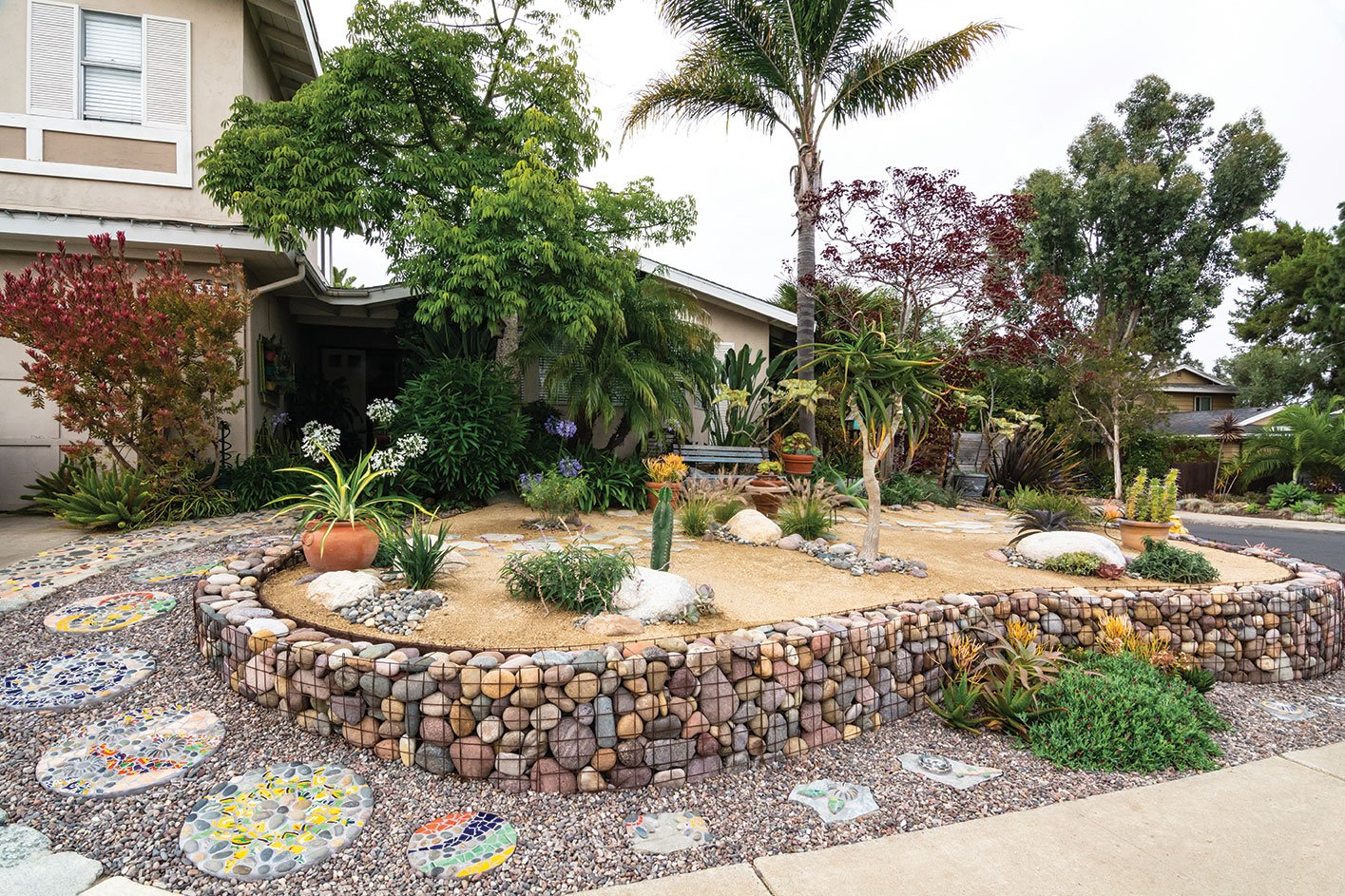 changeable garden with lots of art, mosaic pavers and gravel with succulents and drought tolerant plants