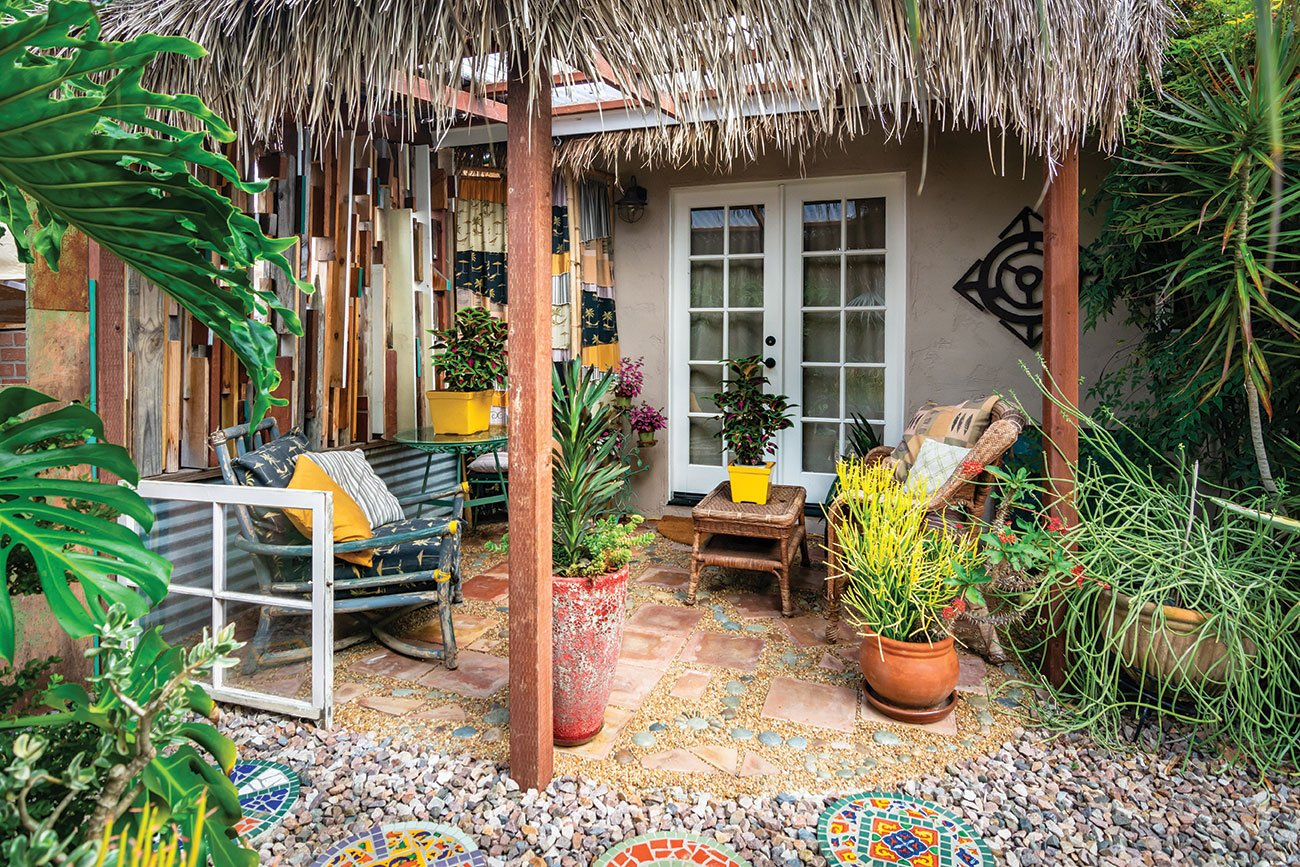 thatched roof patio with pea gravel and mosaic pavers brightly color pots and succulents in a san diego garden