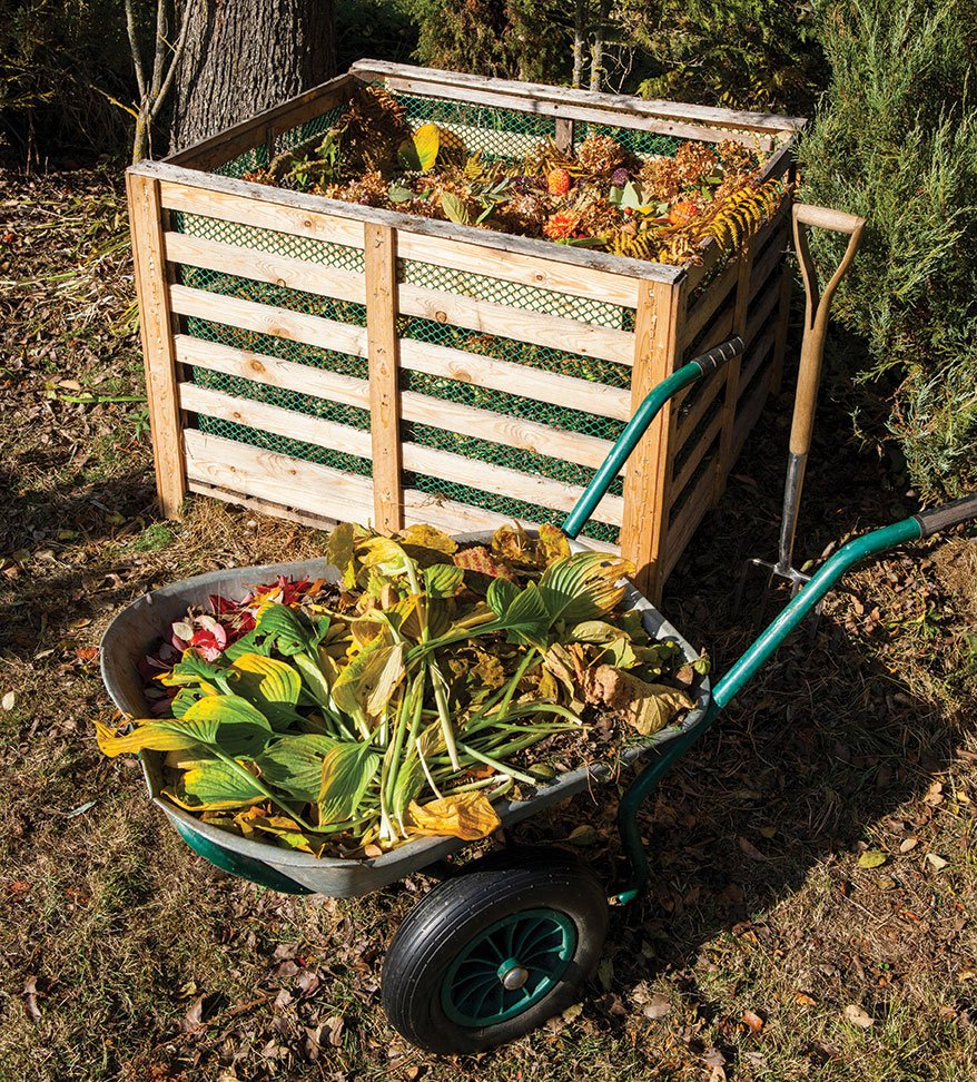 an open-air compost heap in a wooden container with wheelbarrow summer gardening