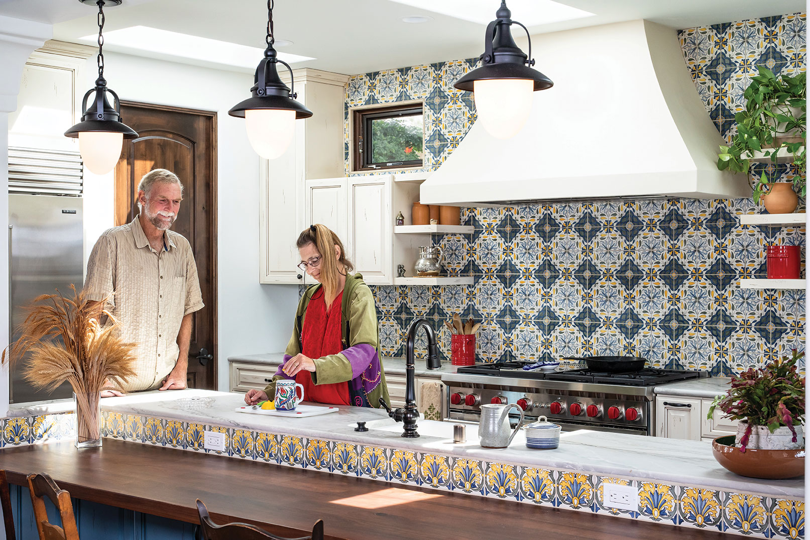a couple prepares tea in an eclectic kitchen with colorful tile in an ocean beach san diego home
