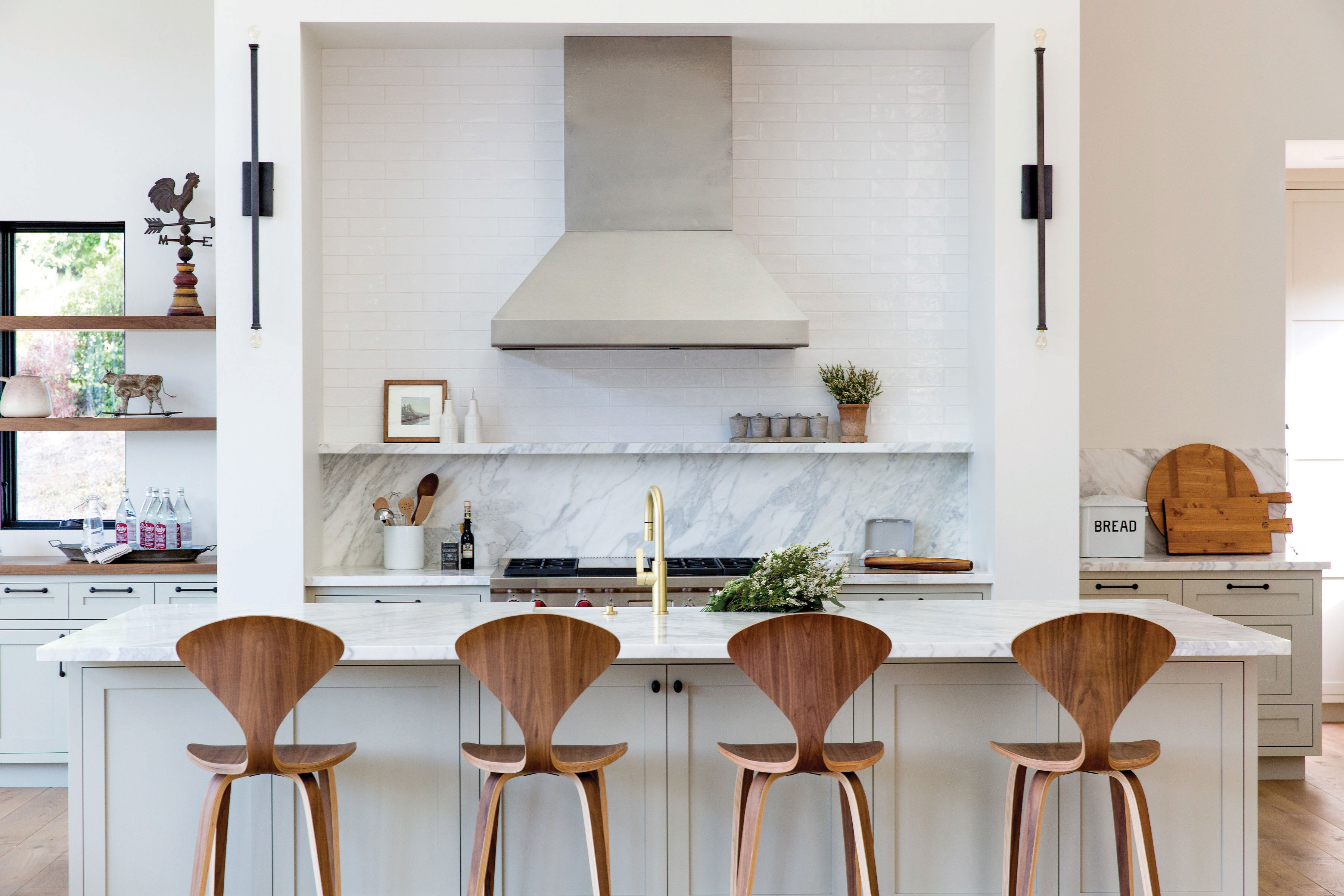 modern farmhouse kitchen mod wooden chairs marble backsplash and gold brass faucet fixtures