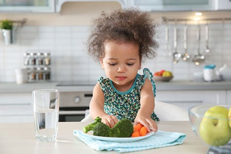 Girl Eating Vegetables 115878204 S