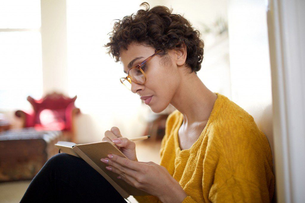 Close Up Young African American Woman With Glasses Writing In Book