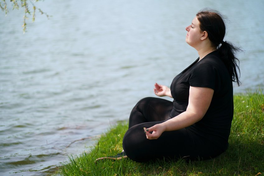 Overweight Woman Meditating Sitting Outdoors