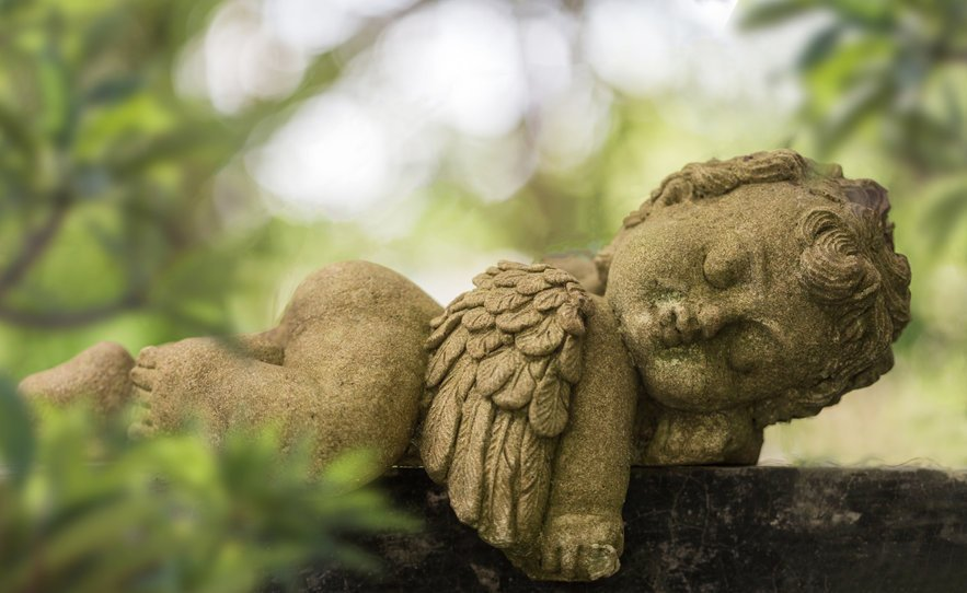 Old Baby Cupid In The Garden, Sculpture At A Melbourne Cemetery.