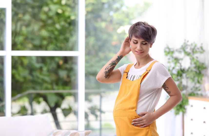 Trendy Pregnant Woman With Tattoos Standing Indoors