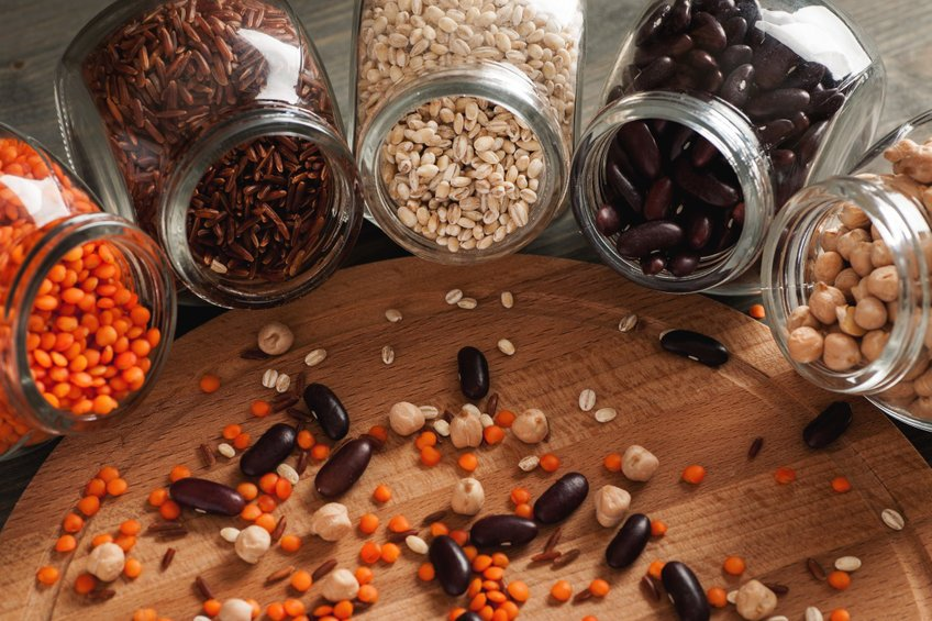Beans And Grain In Glass Jars On A Wooden Table