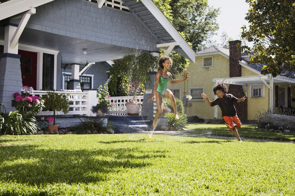 Children Playing In Front Lawn Sprinkler