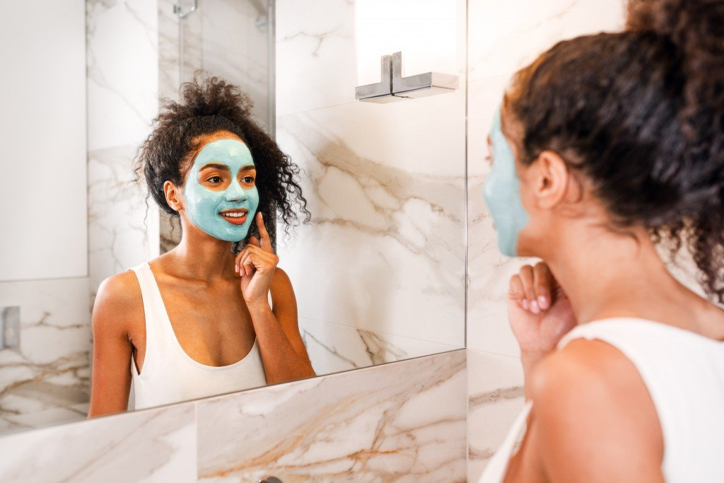 Woman Applying Facial Mask In Front Of Bathroom Mirror