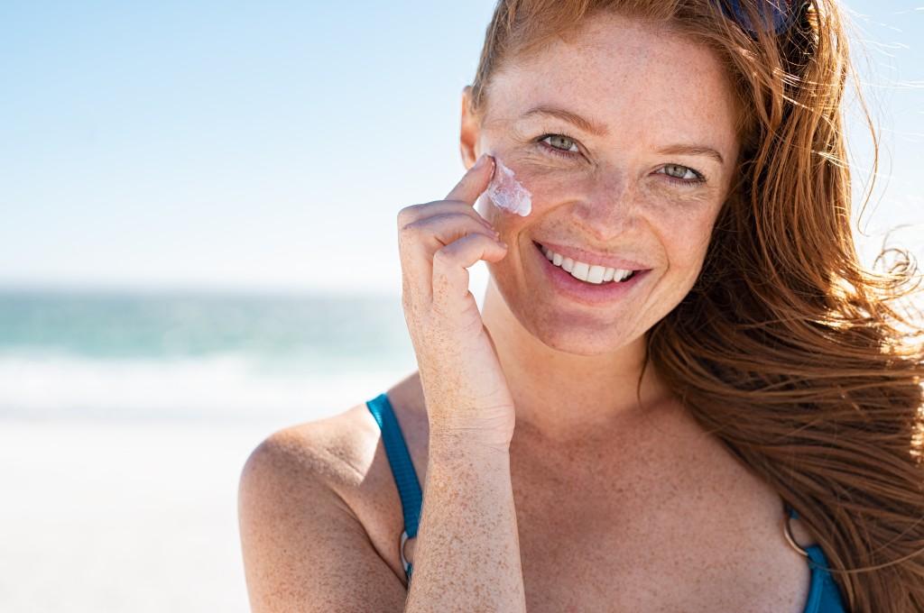 Mature Woman Applying Sunscreen On Face
