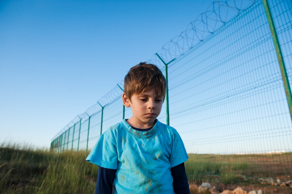 Upset Poor Little Boy Refugee With Dirty Face Near Wall Fence On Border