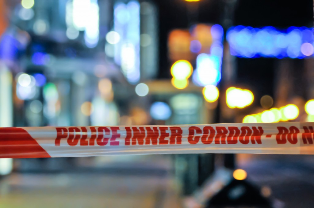 Police Cordon Tape Seals Off An Area Of A City At Night Following A Crime.