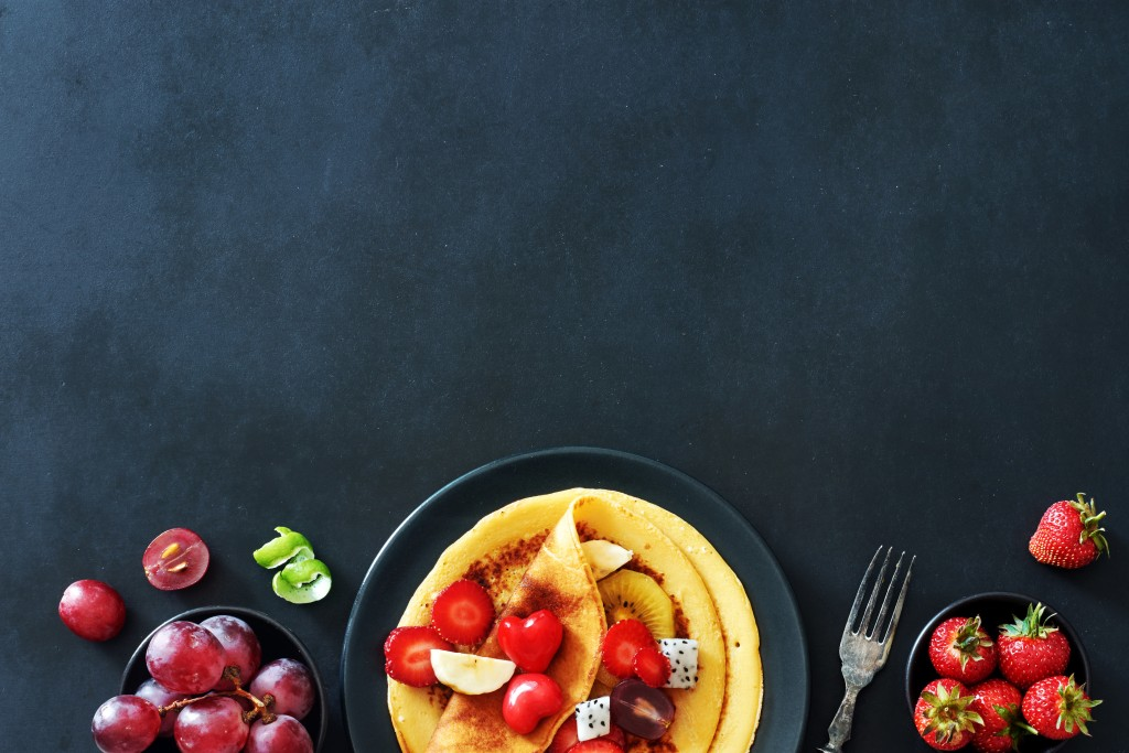 Top View Of Homemade Crepes With Strawberries, Grapes And Honey Over Black Background With A Copy Space.