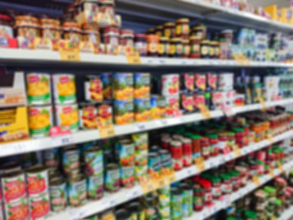 Blurred Abstract Image. Goods On The Shelf Of A Grocery Store. Canned Vegetables And Fruit