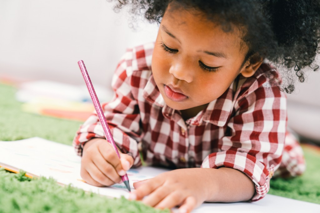 Cute Young African American Kid Girl Drawing Or Painting With Colored Pencil. Kindergarten Children Education, Or Preschool Child Study At Home Concept