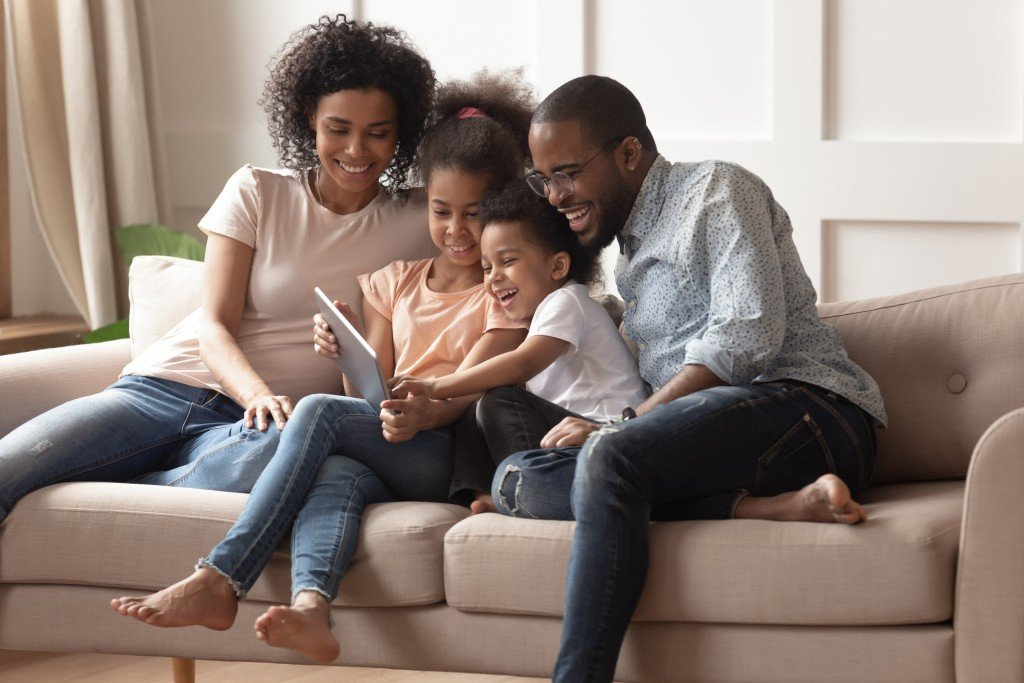 Happy Black Parents And Children Using Digital Tablet On Sofa