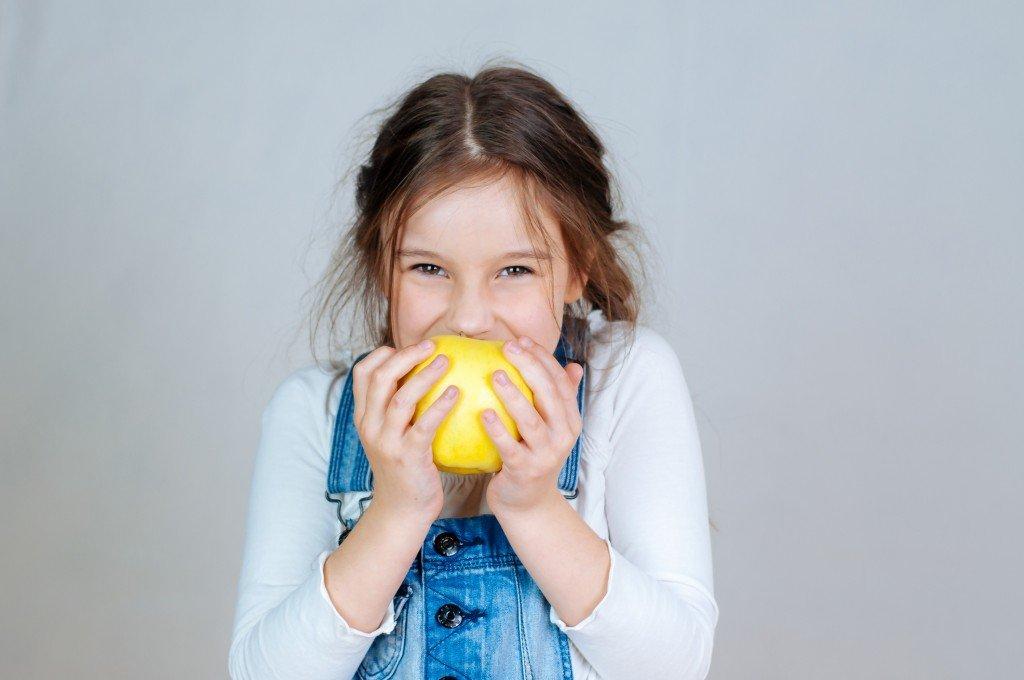 Emotional Portrait Little Beautiful Girl With Pigtails In Jeans Overalls Eating Bites Holding An Apple. 6 7 Years Studio