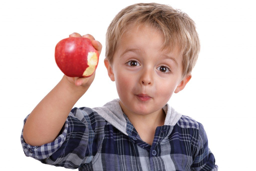 A Little Boy Eating A Red Apple