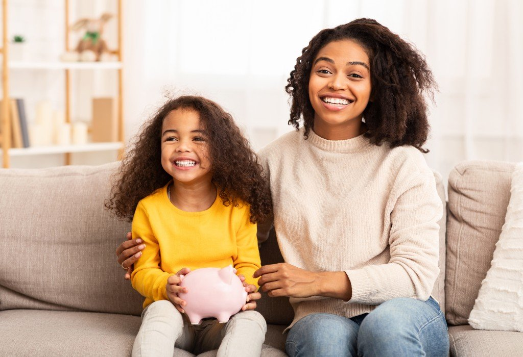 Mother And Daughter Holding Piggybank Sitting On Couch At Home