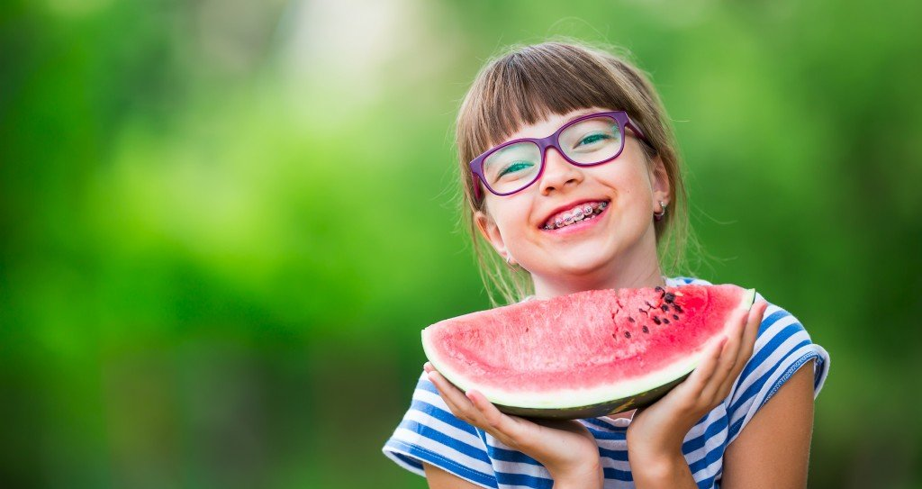 Child Eating Watermelon. Kids Eat Fruits In The Garden.