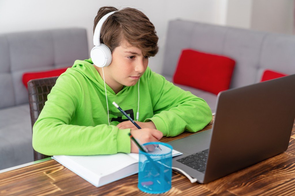 Young Boy Is Studying In Front Of The Laptop. E Learning, Study At Home Online.