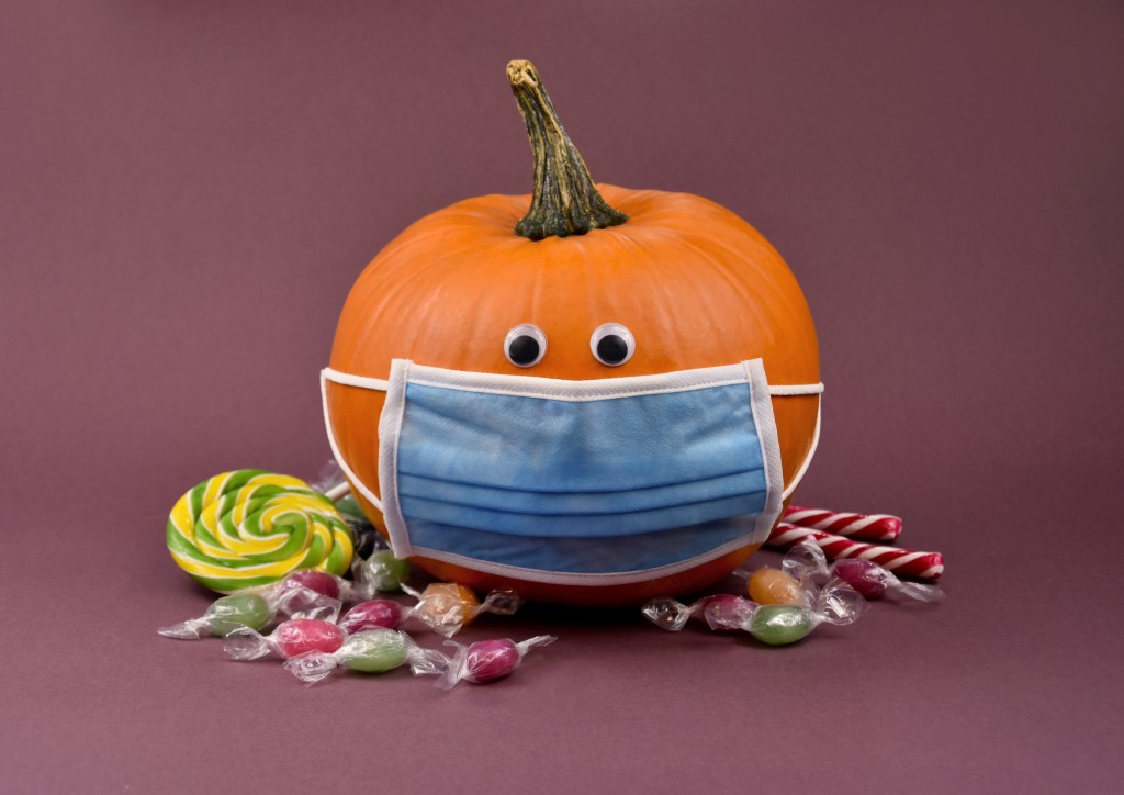 Hallowee Pumpkin With Protective Mask And Candies Stock Images