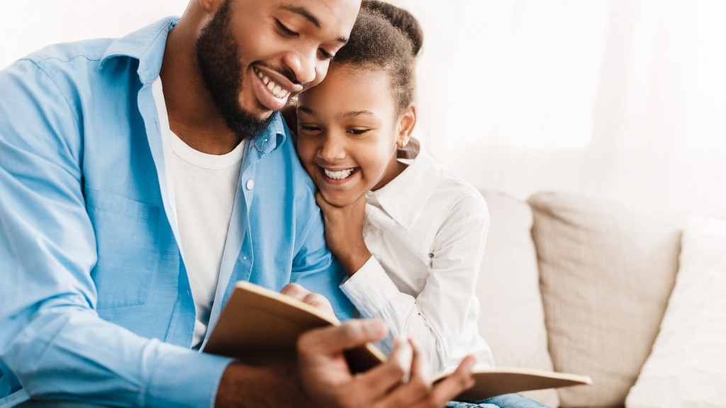 Father And Daughter Reading Book Together At Home