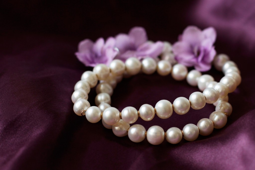 Pearl Necklace On Purple Background